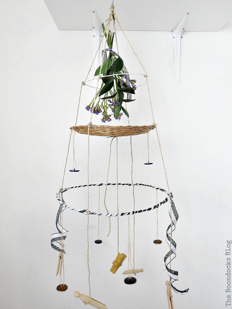 Mobile hanger with three tiers made with wire hangers, a wicker charger and twine, embellished with buttons, ribbon and a bouquet, #Mobile #Hangingart #threetiers #repurposedwirehanger #repurposedbuttons #mobileart #hangingart How to Make a Unique Mobile with Wire Hangers www.theboondocksblog.com