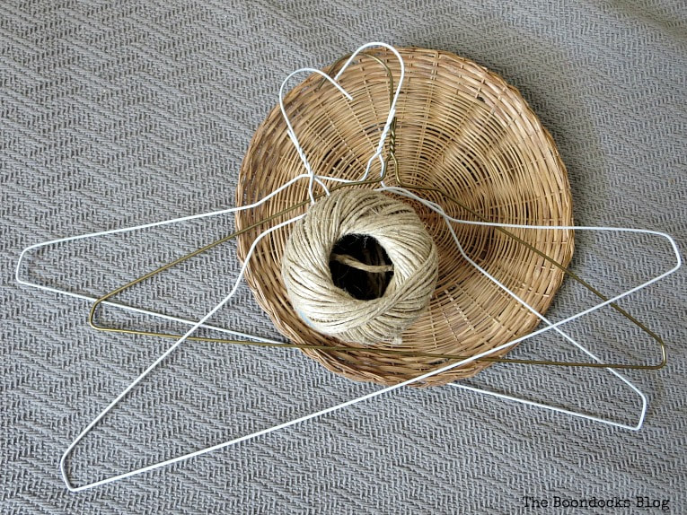 A few hangers, twine and a wicker plate charger, How to Make a Unique Mobile with Wire Hangers www.theboondocksblog.com