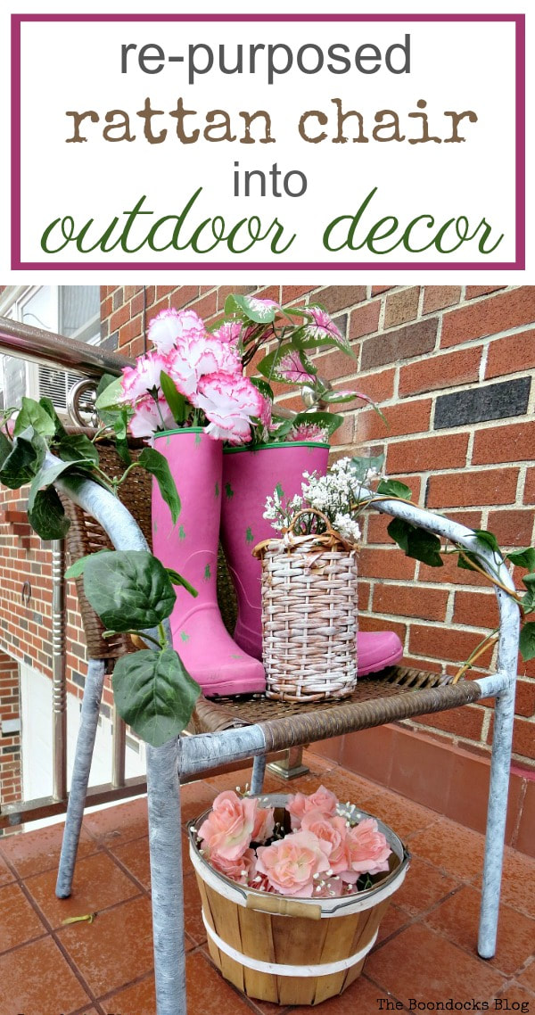 Rattan chair on which boots and wicker bottle holder are placed with flowers for an outdoor decor, #repurposeddecor #outdoordecor #curbappeal #repurposedrubberboots #fauxflowers #easyupcycleddecor #reusingbrokenchair How to re-purpose a torn rattan chair, www.theboondocksblog.com