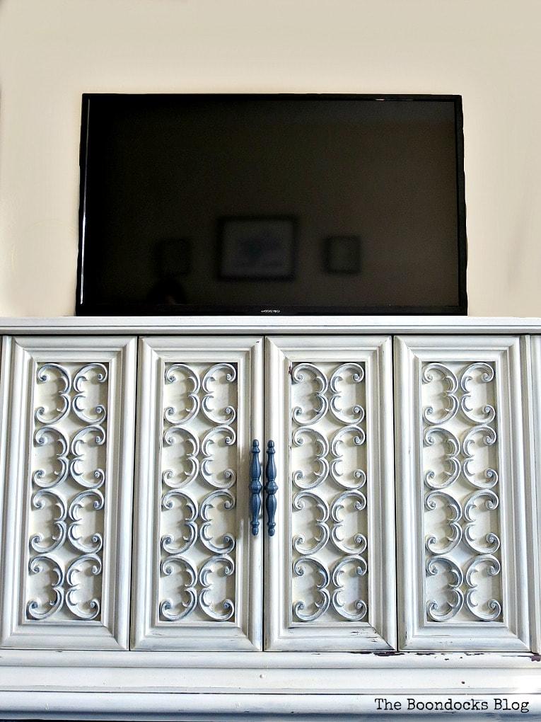 The TV on top of the TV Cabinet now used for storage, #furnituremakeover #Vintagefurniture #SeventiesTVCabinet #OldFashionedMilkPaint #TVCabinetasstorage #ScrollworkonTVCabinet How to Revive a Vintage TV Cabinet www.theboondocksblog.com
