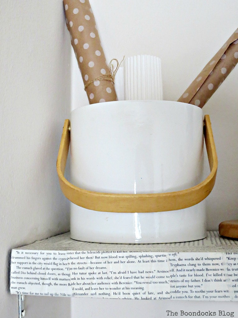 ice bucket repurposed to hold gift wrapping paper, #IkeaLackwallshelf #Modpodge #Decoupageproject #Shelftransformation #Newlookfordarkshelf #Bookpageideas #easyDIYproject How to Change the Look of a Shelf with Book Pages www.theboondocksblog.com