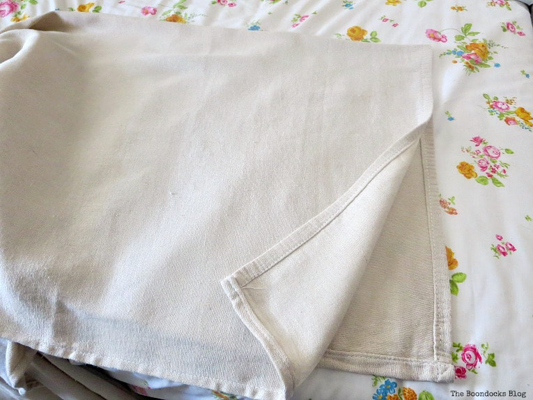 Folding the canvas drop cloth in half, How to Make an Easy No-Sew Bed Skirt with Drop Cloth www.theboondocksblog.com