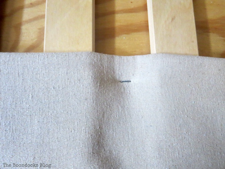 Stapling the canvas drop cloth onto the plywood base of the bed, How to Make an Easy No-Sew Bed Skirt with Drop Cloth www.theboondocksblog.com
