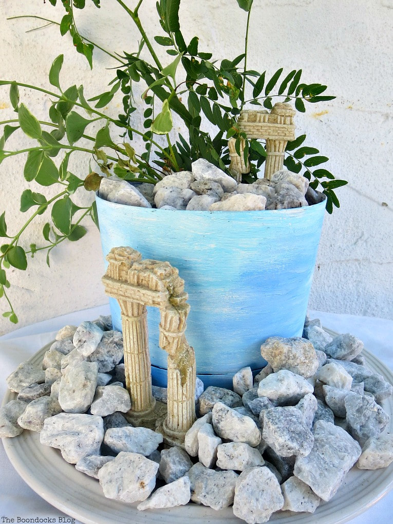 planter with a beachy ancient ruin look, #beachysummerlook #ancientruins #beachyplanter #Mediterranean #plantervignette #containerplanter #pebblerockproject #vincavine #easyproject Using Pebbles to Inspire My Love of the Beach www.theboondocksblog.com