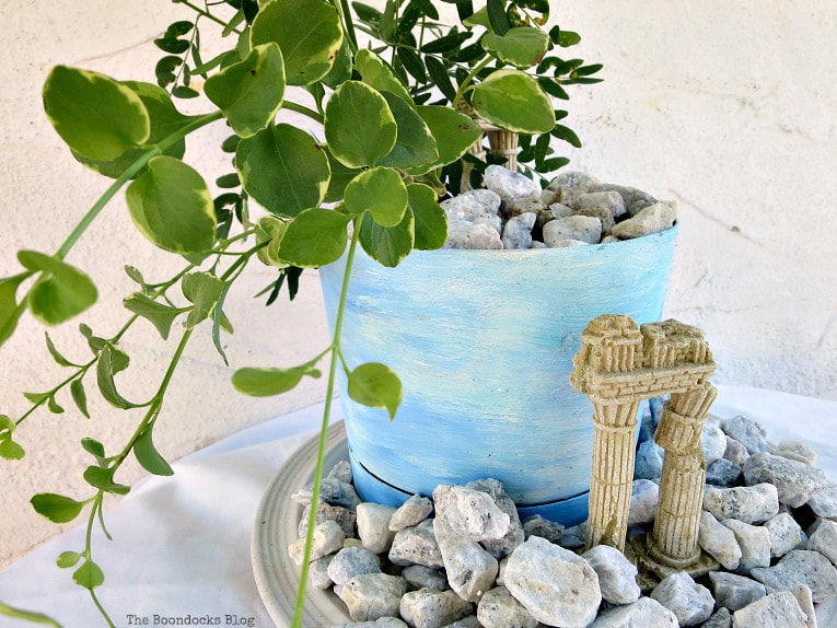 planter with a beachy ancient ruin look, #beachysummerlook #ancientruins #beachyplanter #containerplanter #Mediterranean #plantervignette #pebblerockproject #vincavine #easyproject Using Pebbles to Inspire My Love of the Beach www.theboondocksblog.com