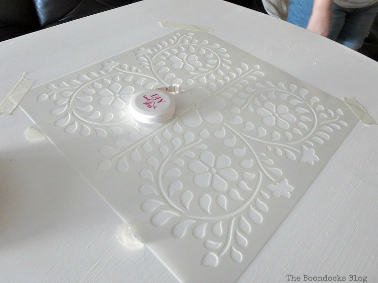 Positioning stencil on table which has been painted white, How to Give your Old Table a New Look with Stencils, the boondocksblog.com
