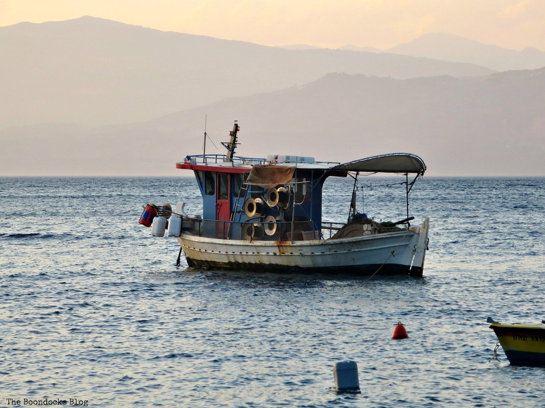 fishing boat in water during sunset, A different look at the beach in Beautiful Greece www.theboondocksblog.com