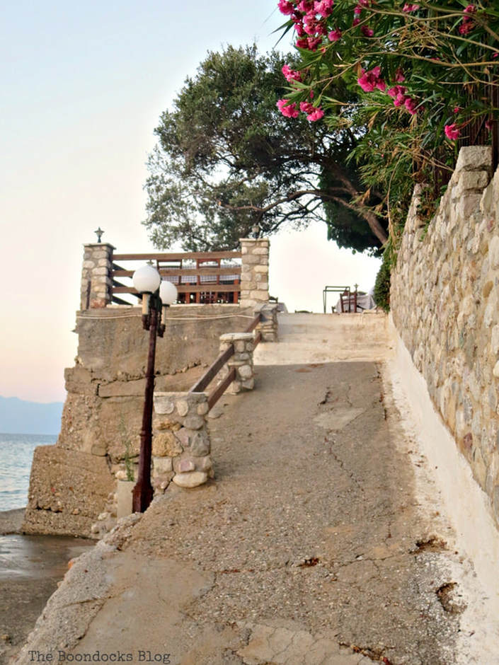 flowers in front of stone wall and walkway, A different look at the beach in Beautiful Greece www.theboondocksblog.com