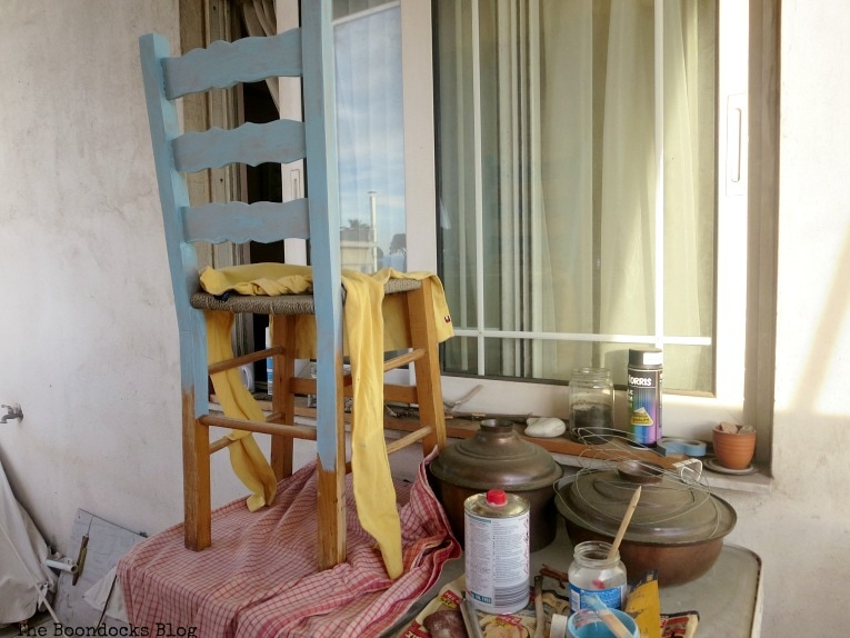 Chair being painted on top of table in balcony, The tale of the Happy Chairs, www.theboondocksblog.com