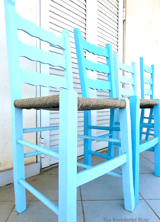 Four wood chairs painted blue lined up side-by-side against a white wall.
