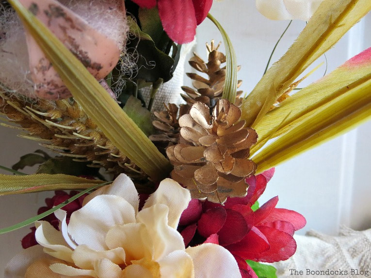 Close up of pine cones, wheat grass and flowers.