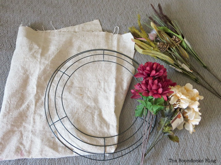 Items used to make wreath, wire form, flowers and fabric, How to Make a Simple Dollar Store Fall Wreath www.theboondocksblog.com