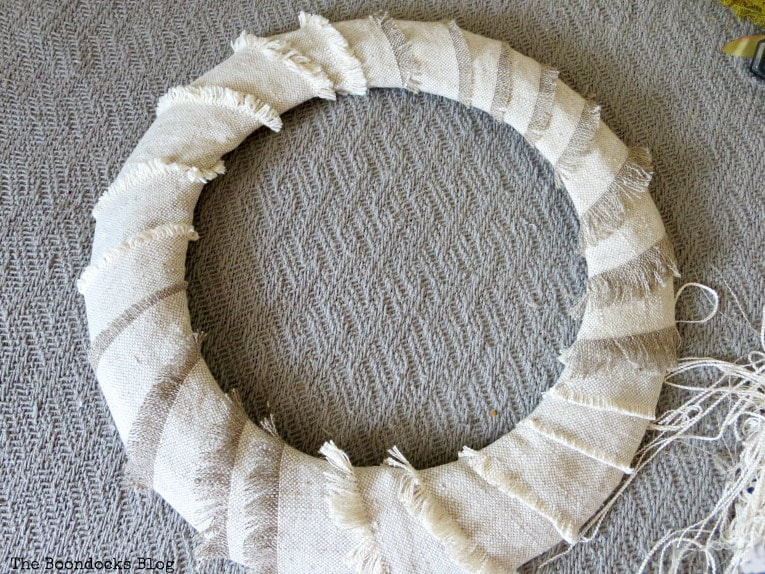 strips of fabric wrapped around the wire form, How to Make a Simple Dollar Store Fall Wreath www.theboondocksblog.com