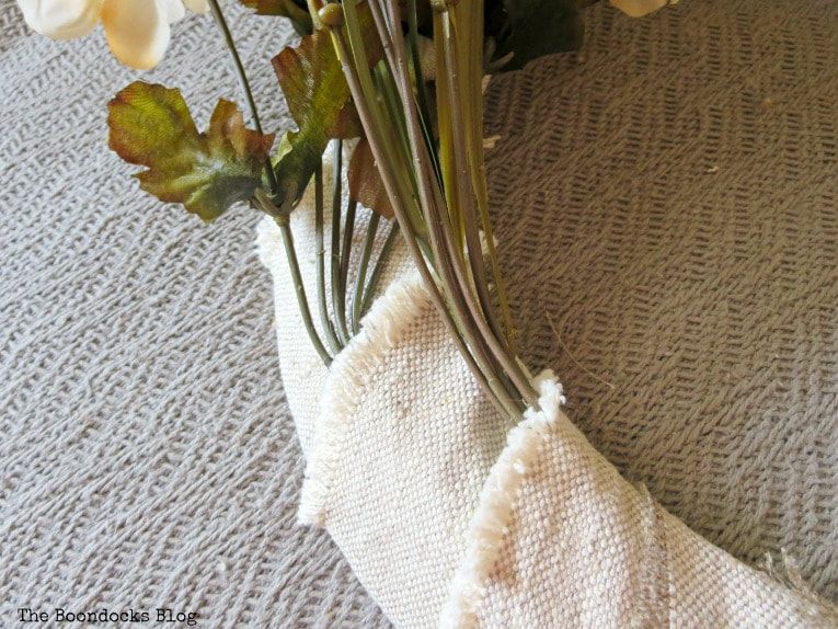 Placing the faux flowers into the fabric strips on the wire form.