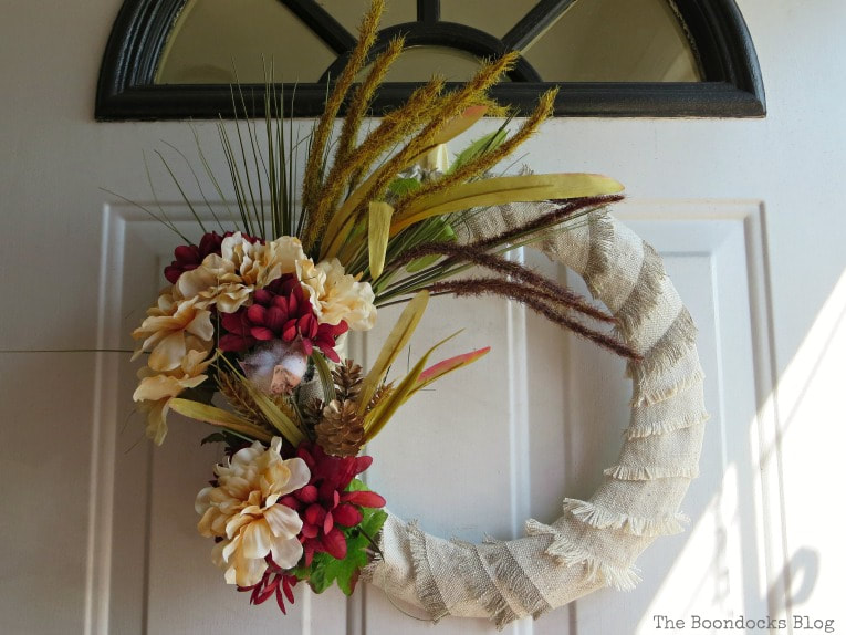 Hanging the wreath on the front door, How to Make a Simple Dollar Store Fall Wreath www.theboondocksblog.com