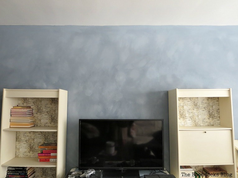 Two shelves and a TV placed infront of an accent wall with cloudy effect.