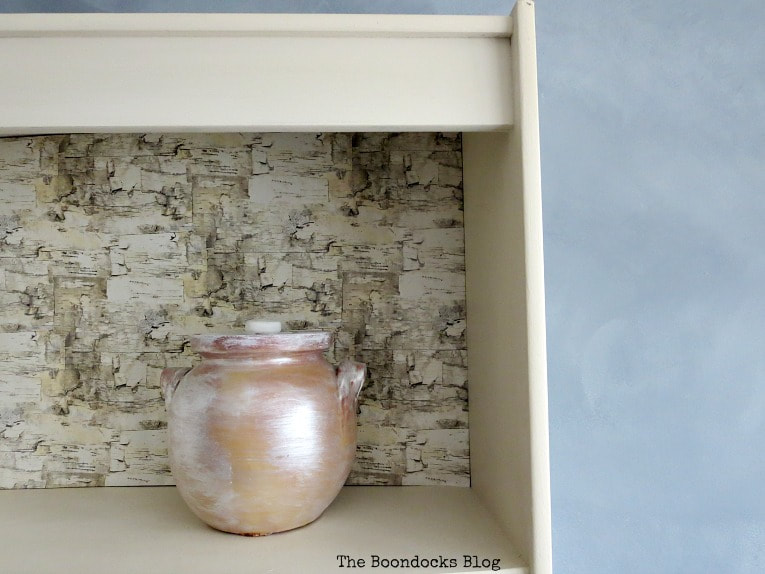 White bookcase shelf with birch wrapping paper backing and a painted pot placed on the shelf.