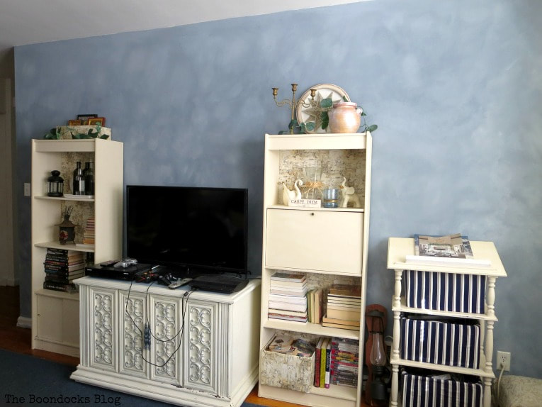 Finished living room with furniture, TV and bookcases placed in front of the cloudy painted accent wall.
