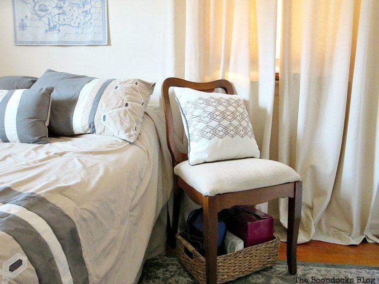 Chair beside bed with basket underneath, How to Create a Calm Look for a Bedroom www.theboondocksblog.com