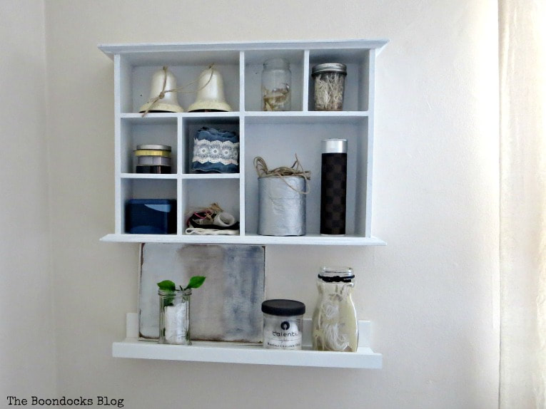 Ikea picture ledge below a wall mounted storage caddy, How to Create a Calm Look for a Bedroom www.theboondocksblog.com