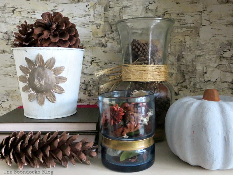 Fall vignette with pine cones, pumpkin, potpourri and bucket, How to Style a Bookcase for Fall 3 Different Ways www.theboondocksblog.com