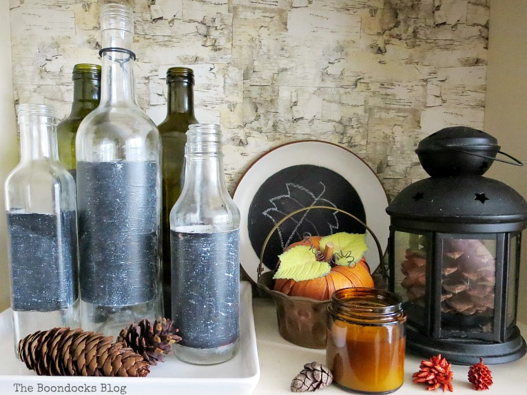 Fall vignette with glass bottles pine cones and pumpkin, How to Style a Bookcase for Fall 3 Different Ways www.theboondocksblog.com