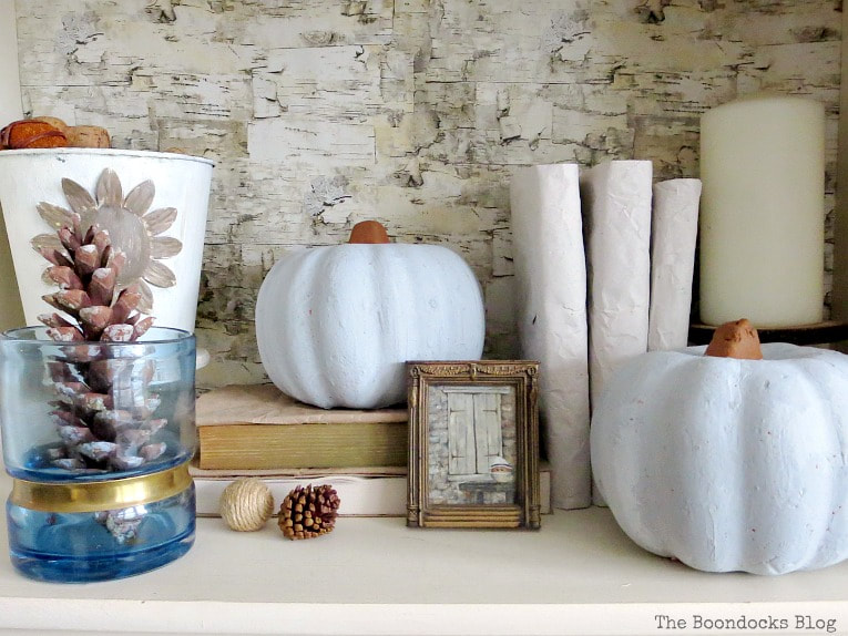 Fall vignette with blue vase, books, pine cones, pumpkins, art and a candle, How to Style a Bookcase for Fall 3 Different Ways www.theboondocksblog.com