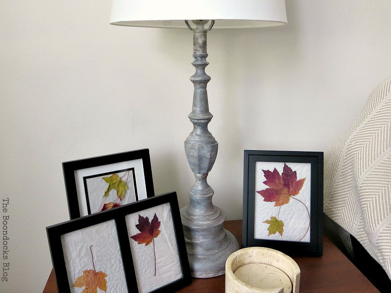 Painted lamp base on wood table with framed pictures of leaves.
