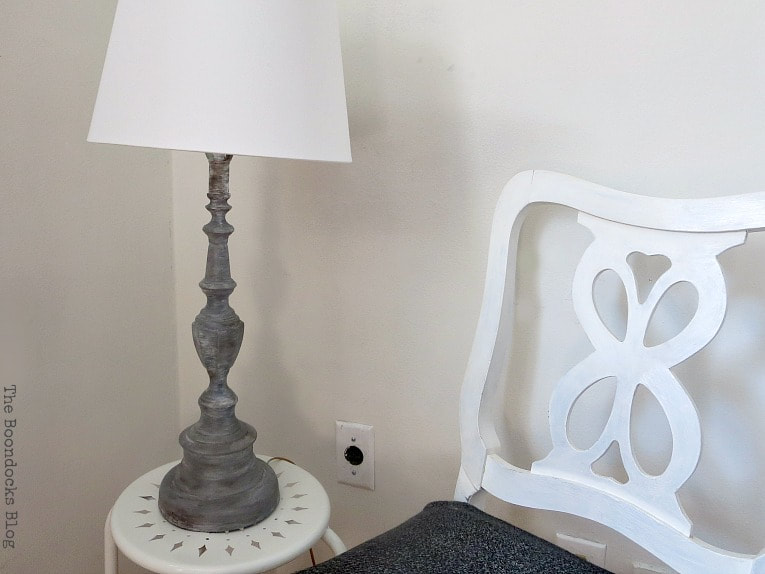 Finished painted lamp sitting on a white table and beside a white chair.