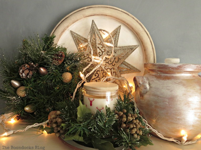 top of bookcase with star ornament, candle, ceramic pot and wreath, How to Reuse Old Decor to Make Bright Christmas Vignettes www.theboondocksblog.com