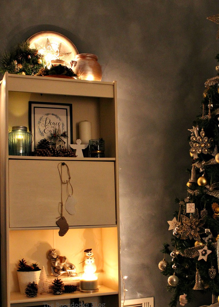 Nighttime view of bookcase, How to Reuse Old Decor to Make Bright Christmas Vignettes www.theboondocksblog.com