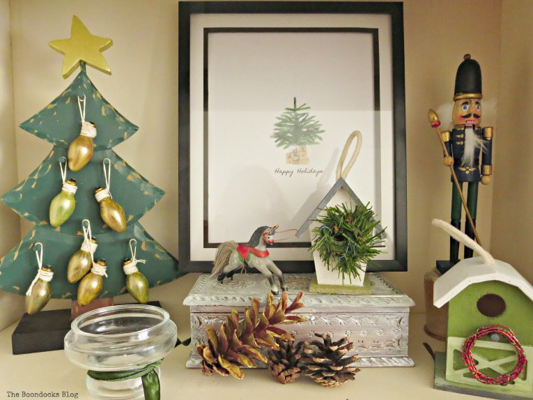 Green composition on bookcase, How to Reuse Old Decor to Make Bright Christmas Vignettes www.theboondocksblog.com