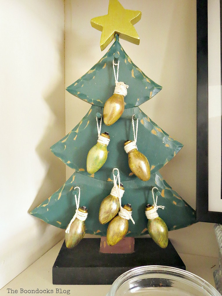 Green wooden tree with light bulbs painted gold, How to Reuse Old Decor to Make Bright Christmas Vignettes www.theboondocksblog.com