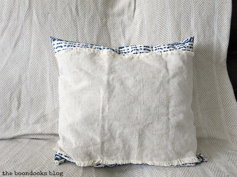 finished pillow with linen on one side. How to Make Easy Pillows out of Fabric Remnants 5 ways www.theboondocksblog.com