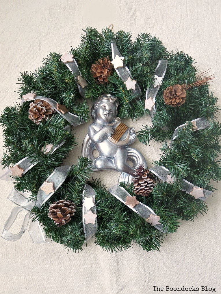Wreath with ribbon and metallic stars and cherub with harp, #christmaswreath #holidaywreath #winterywreath #upcycle #metallicaccentwreath #easycraft #christmascraft #holidaycraft #metalliccherub How to Make a Christmas Wreath with Metallic Accents, www.theboondocksblog.com
