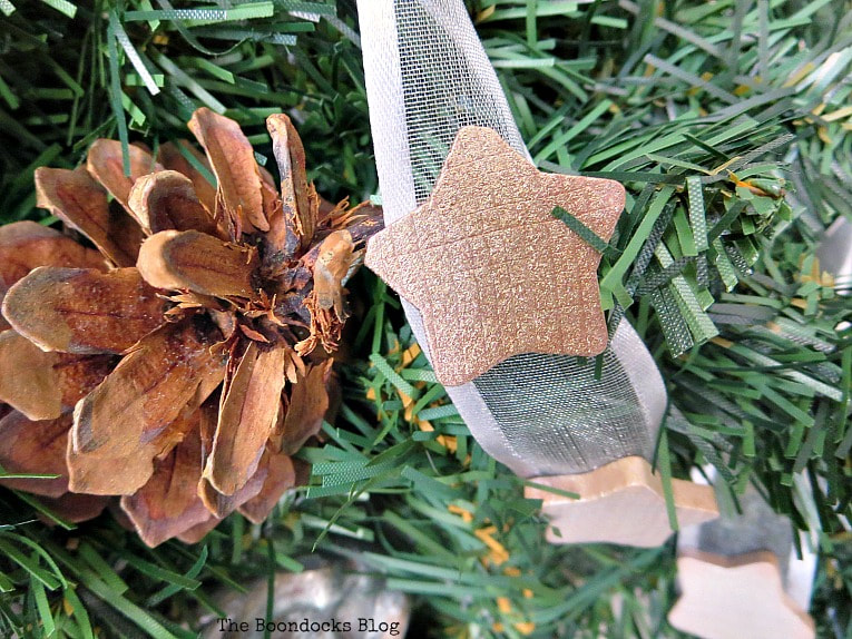 brown metallic star next to pine cone, How to Make a Christmas Wreath with Metallic Accents, www.theboondocksblog.com