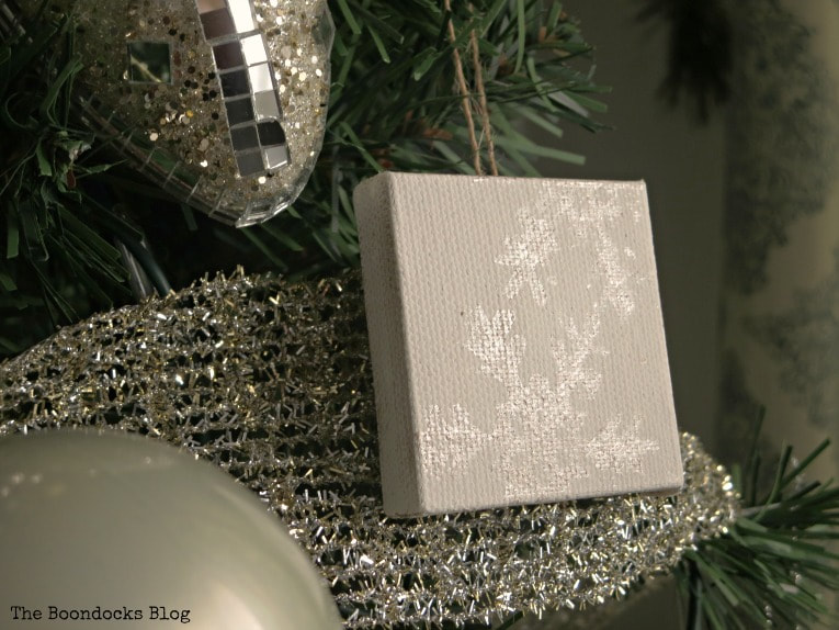 snowflake design shining on mini canvas, How to Make Easy Snowflake Mini Canvas Ornaments www.theboondocksblog.com