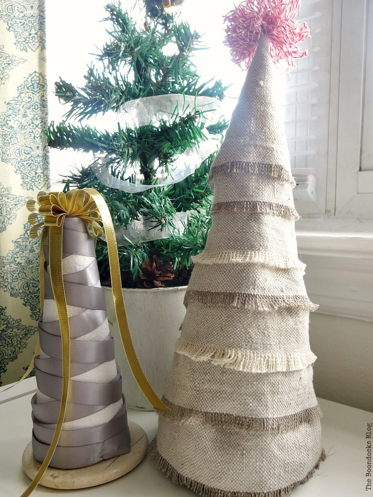 Mini Christmas tree made with fabric scraps beside a grey and gold ribbon wrapped into a Christmas tree shape. Both are placed in front of a miniature potted evergreen tree.