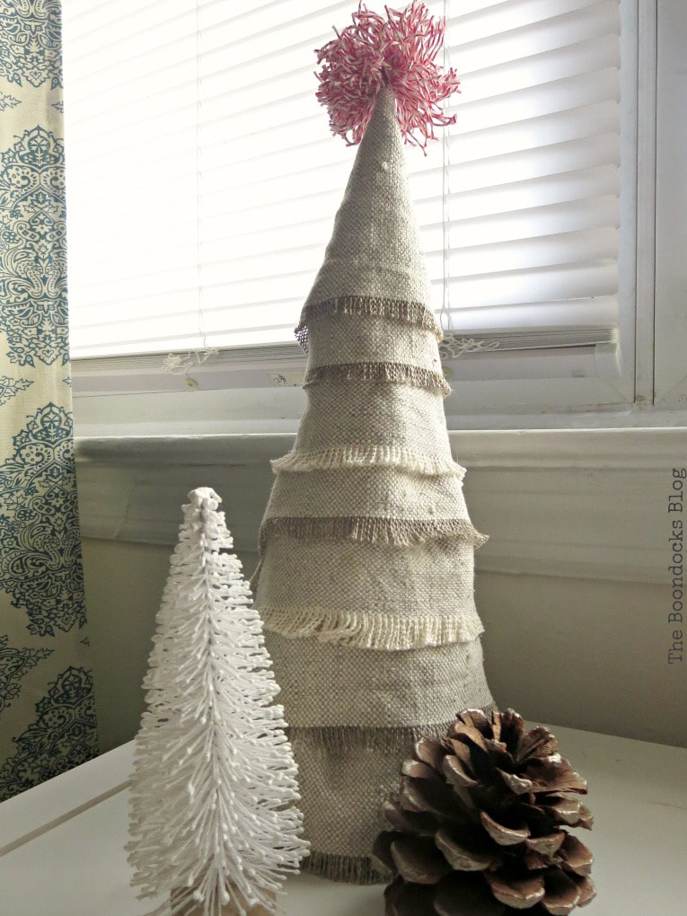 Mini Christmas tree made with fabric scrap fabric beside a miniature white tree and a pine cone.