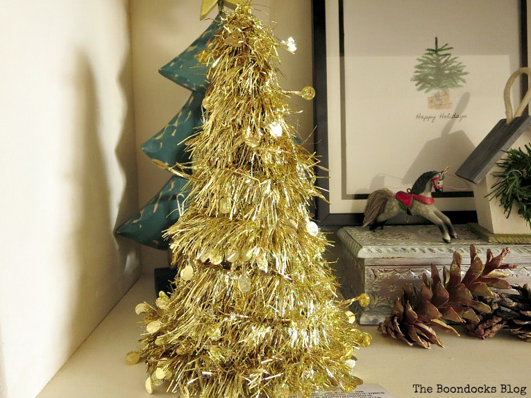 Gold Tinsel mini tree bought beside a mini horse decoration, pine cones and a framed picture.