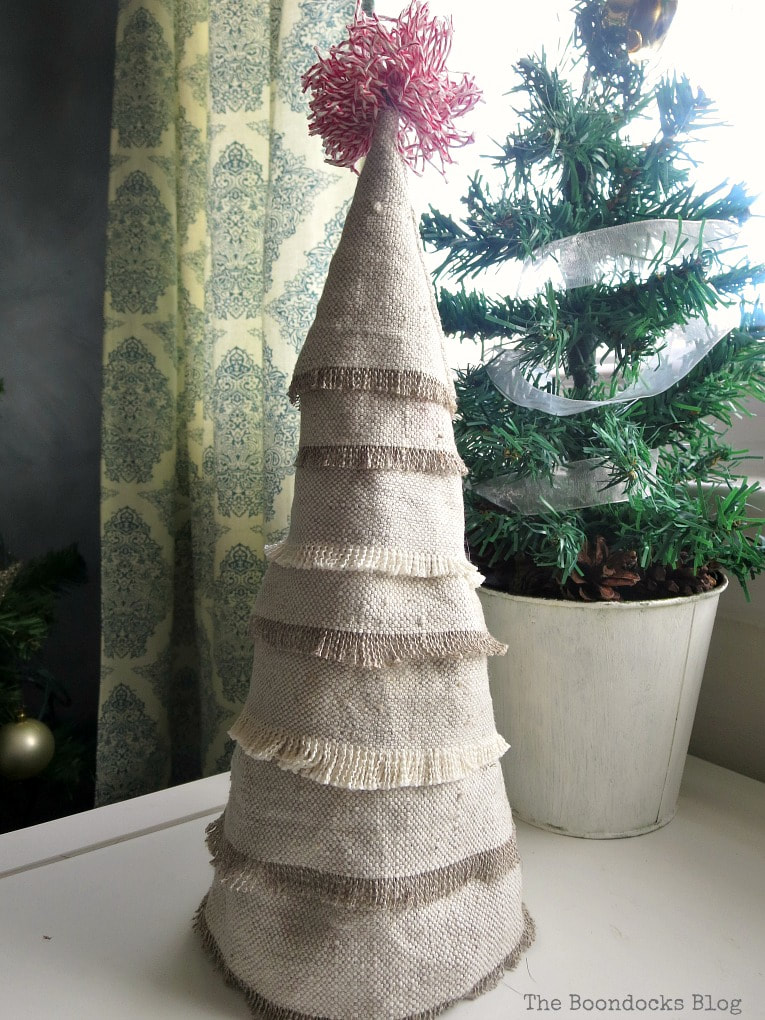 Mini Christmas tree made with fabric scraps, placed in front of a mini potted evergreen tree.