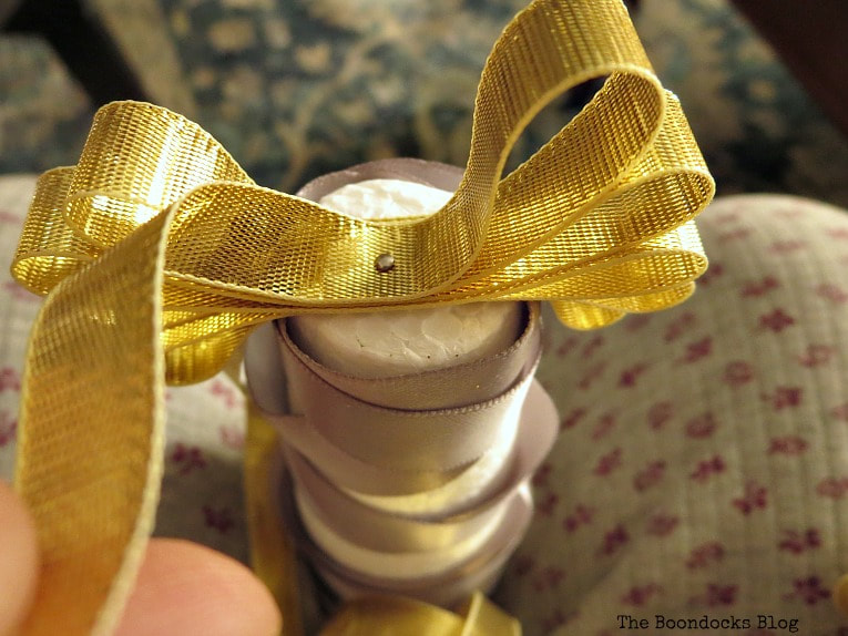 Gold ribbon secured with a pin to form bow, How to Make a Simple Mini Christmas Tree with Ribbon www.theboondocksblog.com