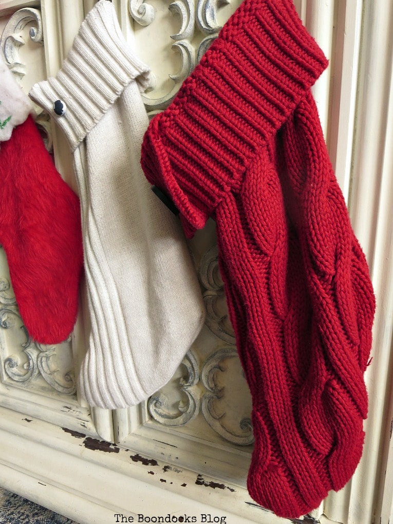 Sweater stockings hanging on tv cabinet, #repurposing #repurposedsweaters #Christmasstockings #easycraft How to Make Easy Christmas Stockings from Sweaters www.theboondocksblog.com