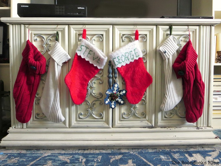 Christmas Stockings hung from the TV cabinet. How to Make Easy Christmas Stockings from Sweaters www.theboondocksblog.com