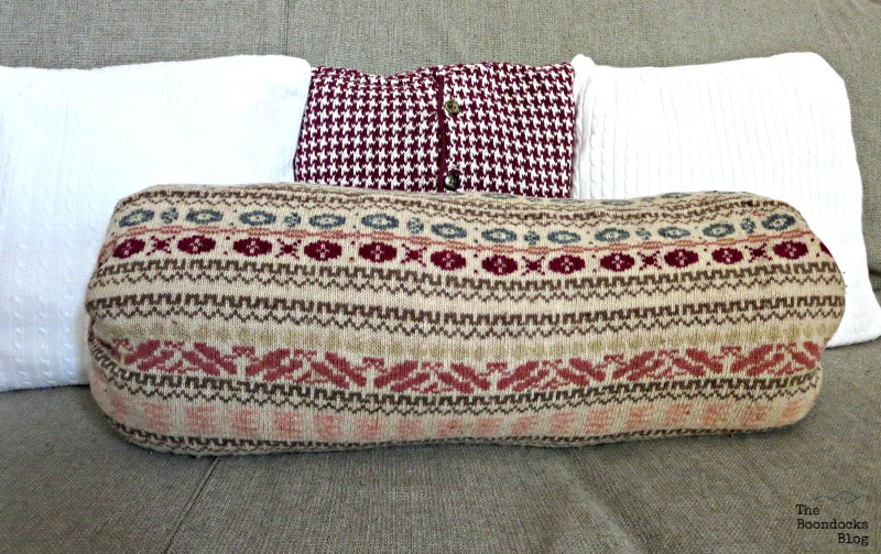 re-purposed sweater as bolster pillow, 15 Ways to Re-purpose Old Clothes into Something New www.theboondocksblog.com