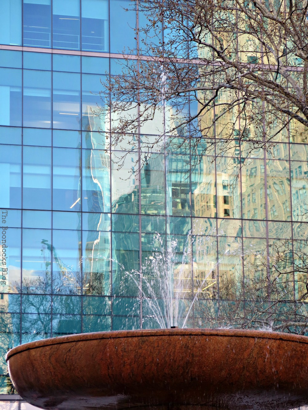 Reflections on Glass facade of skyscraper and the water fountain at the forefront, Bryant Park New York, A Visit to the Restored Bryant Park and its Surrounding Areas www.theboondocksblog.com