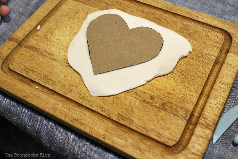 placing cardboard cutout on top of clay, How to Make a Natural Clay Valentine's Heart Garland www.theboondocksblog.com