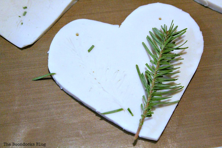 Adding pine branches for more texture, How to Make a Natural Clay Valentine's Heart Garland www.theboondocksblog.com
