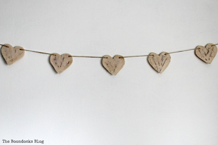 finished heart garland on wall, How to Make a Natural Clay Valentine's Heart Garland www.theboondocksblog.com