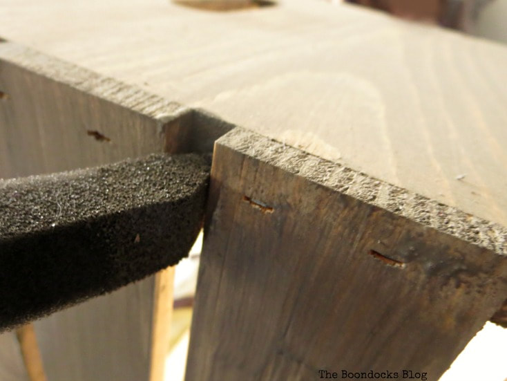 Close up image of applying barnwood stain in between the slats of the wooden crate.